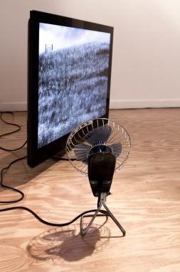Zephyr is an installation closely related to the exhibition's title. A modified desk fan, fitted with a slowly rotating motor faces a large screen. A looped video reveals the undulating movement of wind caressing a hillside of flowering grasses, time slows down, movements unfold slowly, seemingly conducted by the fan's considered rotations.